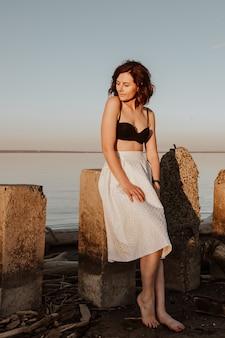 Позирующая женщина на природе. молодая женщина в стильной одежде: топ и белая юбка, сидя на камнях на фоне моря.