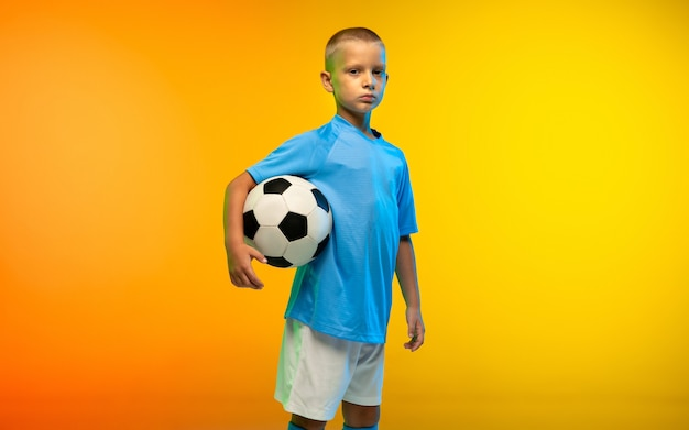 Posing. young boy as a soccer or football player in sportwear practicing on gradient yellow in neon light
