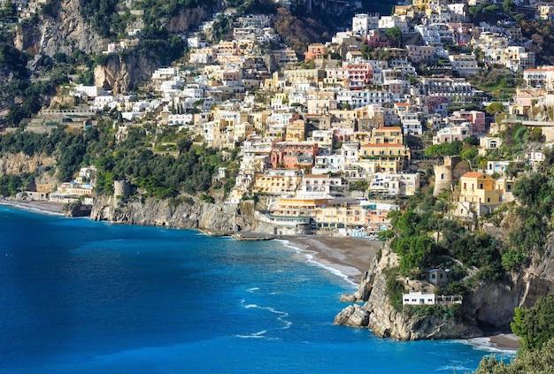 岩だらけの丘のポジターノ村の海岸の景色。イタリア、アマルフィ。