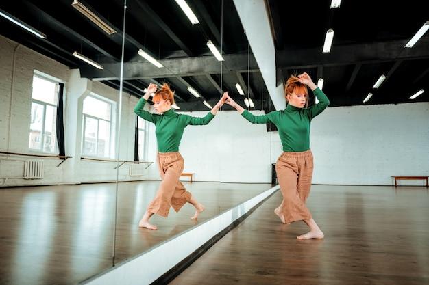 Должность. довольно рыжая профессиональная танцовщица в зеленой водолазке стоит в танцевальной позе