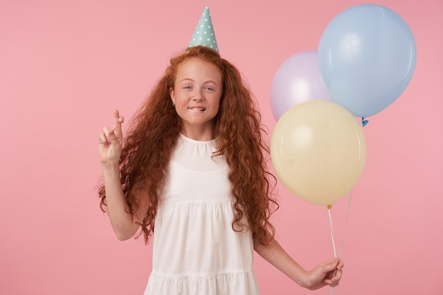 気球でピンクの背景の上にポーズをとる、交差した指で手を上げる、彼女の誕生日に願い事をする、真のポジティブな感情を表現する長いセクシーな髪のポジティブな巻き毛の少女