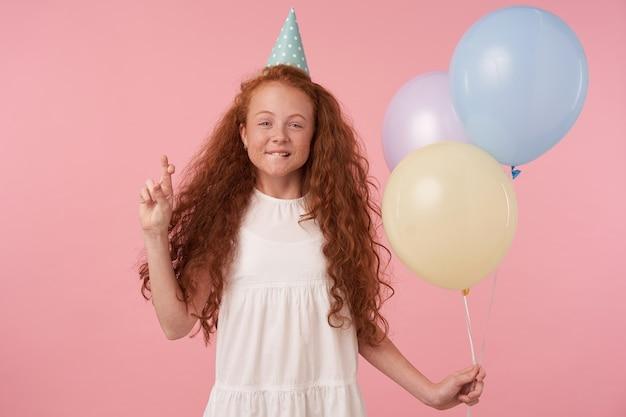 Posititve bambina riccia con lunghi capelli volpi in posa su sfondo rosa con mongolfiere, alzando la mano con le dita incrociate, esprimendo un desiderio per il suo compleanno, esprimendo vere emozioni positive