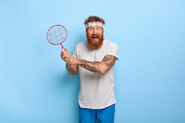 Позитивно-активный мужчина играет в теннис или бадминтон, имеет забавное радостное выражение лица, держит в руках ракетку, носит белую повязку на голову