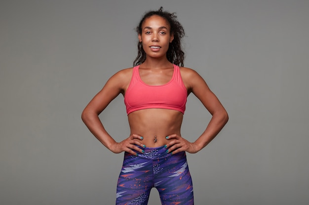 Positive active young dark skinned curly brunette woman with belly button piercing looking cheerfully while standing. fitness and sport concept