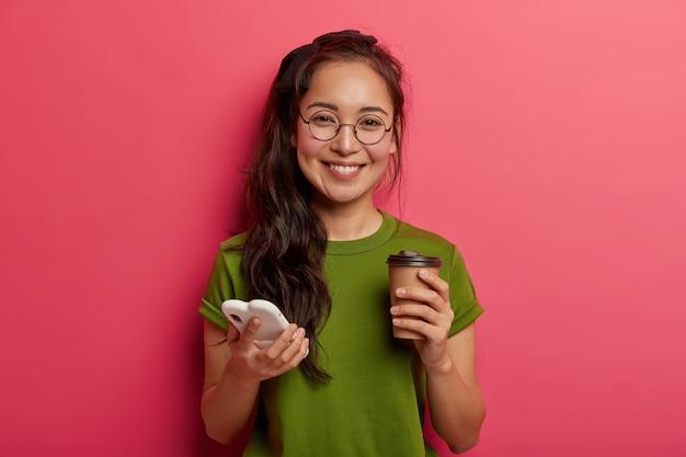 Positiva adorabile ragazza etnica scorre le foto nello smartphone, utilizza lo smartphone moderno e beve caffè da asporto, si sente toccata e felice, indossa occhiali rotondi, utilizza il sito web per lo shopping