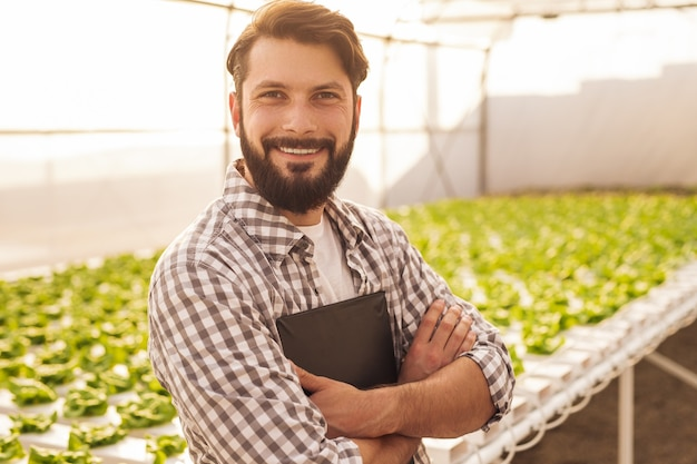 Positive adult bearded male farmer in checkered shirt with clipboard in hands smiling and looking at camera, while working in agricultural greenhouse with green sprouts growing in hydroponic tanks