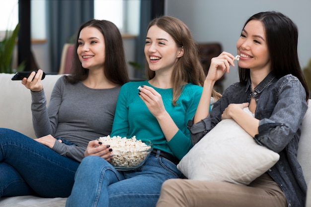 Positive adult women watching series together