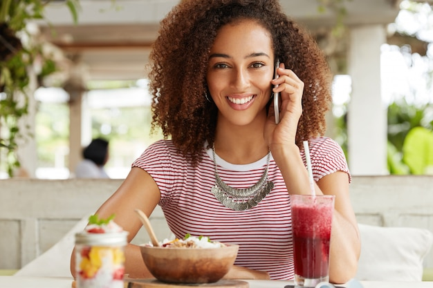 Positive african american female has broad shining smile, communicates via cell phone during dinner break in exotic cafe, has pleasant conversation with relatives, shares impressions about vacations