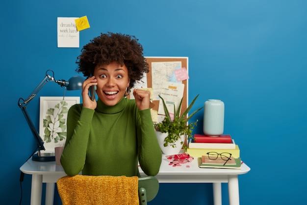 긍정적 인 아프리카 계 미국인 여성은 스마트 폰으로 이야기하면서 주먹을 움켜 쥐고, 기뻐하고, 크게 웃으며, 집에서 재무 보고서를 작성합니다.