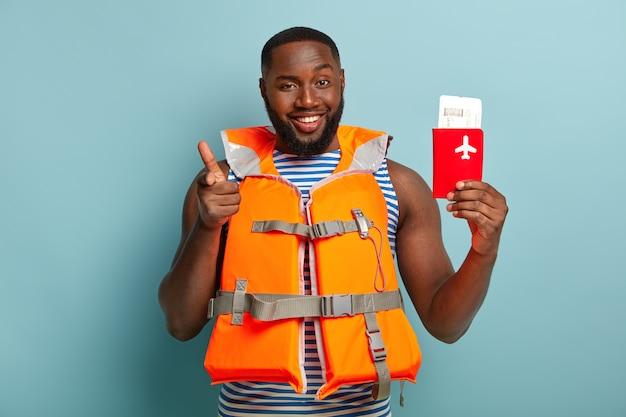 Il viaggiatore maschio afroamericano positivo ti indica, suggerisce di viaggiare con lui all'estero, detiene il biglietto di viaggio e il passaporto