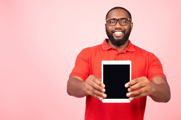 Positive african american man holding tablet and showing it blank screen