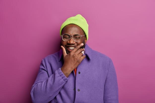 ポジティブなアフリカ系アメリカ人の男性は、あごを持って、楽しく笑い、大喜びし、陽気な会話をし、帽子をかぶっています