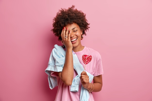 ポジティブなアフリカ系アメリカ人の10代の少女は、顔を手のひらにし、楽しんで、カジュアルな服を着て、ハート型のロリポップを持って、暇な時間を楽しんで、ピンクの壁に向かってポーズをとります。菓子のコンセプト