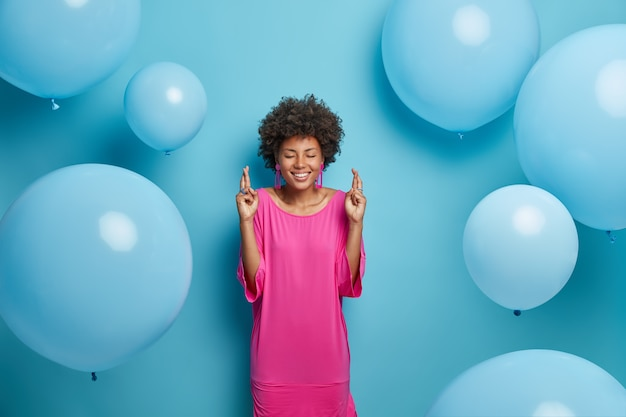 Positive african american woman in elegant pink dress, crosses fingers and anticipates for something desirable happen, being on party, poses against blue wall with inflated balloons around