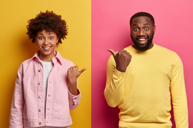 Positive african american woman and man point thumb at each other, smile and look enthusiastic, dressed in casual clothes, isolated on pink and yellow wall, have happy mood, friendly relations