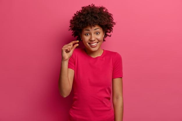 긍정적 인 아프리카 계 미국인 여성은 매우 작거나 작은 것을 보여주고, 매장에서 가격을 논의하고, 행복하게 미소를 짓고, 캐주얼 한 옷을 입고, 분홍색 벽에 고립 된 채 조금 말한다. 크기 개념.
