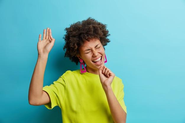 Positive african american woman sings song keeps hand as if microphone has fun has happy mood