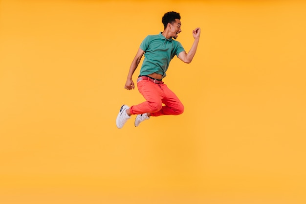 Positive african man in green t-shirt jumping. indoor shot of blissful black guy expressing happy emotions.