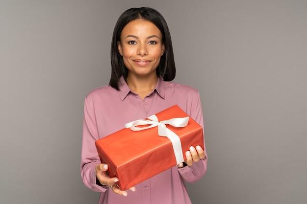 크리스마스 새해나 생일 선물을 손에 들고 있는 긍정적인 아프리카 여성