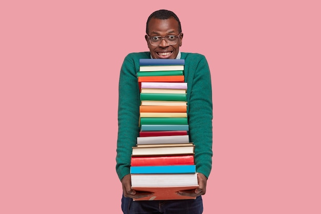 Positive afro american guy holds large pile of textbooks, smiles broadly, wears spectacles and green sweater, isolated over pink background, prepares for lesson