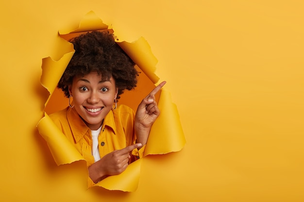 Positive afro american lady shows something amazing, points up and sideways with index fingers, advertises copy space, has toothy smile, isolated over yellow background