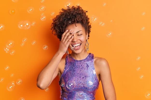 ポジティブなアフリカ系アメリカ人の女性が顔を手の笑顔で覆い、シャボン玉が周りにあるオレンジ色の壁に隔離されたスタイリッシュな服を着た完璧な白い歯を広く持っています