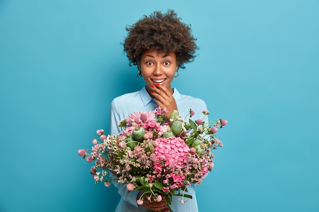 Positive afro american woman holds beautiful bouquet of different flowers