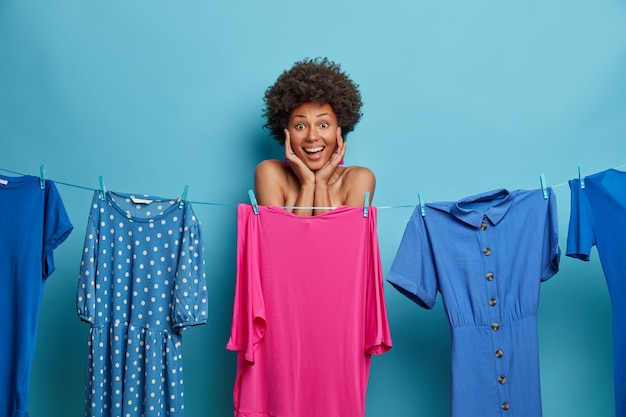 Positive afro american woman keeps hands on face, hides naked body behind pink dress on rope, thinks what to wear for date, isolated on blue wall. fashion, style, dressing and women concept
