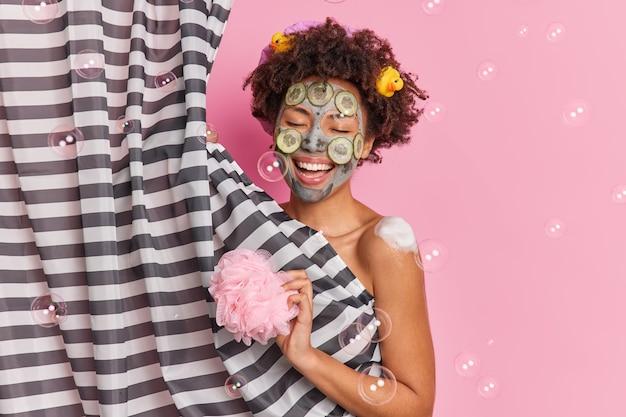 ポジティブなアフリカ系アメリカ人の女性が歌を歌い、シャワーを浴びながらキュウリのフェイシャルマスクを適用して肌を若返らせ、スポンジを保持し、ピンクの壁のシャボン玉に隔離されたボディケア手順を楽しんでいます
