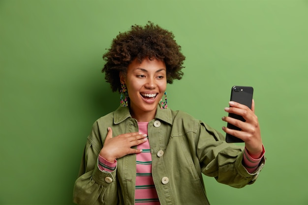 Positive afro american woman smiles at smartphone camera enjoys video calling dressed in fashionable jacket isolated over green wall