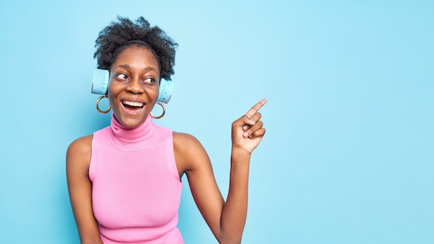Positive afro american woman with curly hair indicates at blank space