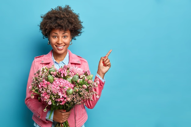 Positive afro american woman with toothy smile indicates aside holds bouquet of flowers