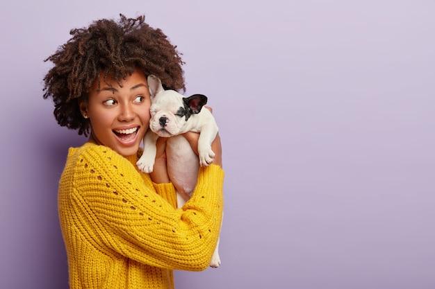 노란색 점퍼를 입은 긍정적 인 아프리카 소녀는 검은 귀를 가진 작은 강아지를 안고 귀여운 애완 동물과 놀며 활력과 기쁨을 느낍니다.