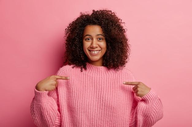 Позитивная афро-девушка показывает на себя, показывает на грудь, хвастливо смотрит, одета в вязаный джемпер оверсайз, делится хорошими новостями, приятно улыбается, изолирована от розовой стены