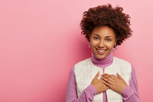 Positive afro woman presses hands on chest, appreciates heartwarming words, smiles gently isolated over pink wall