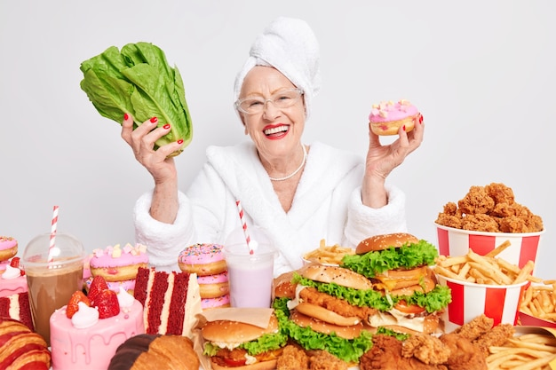 긍정적인 나이 든 유럽 여성은 맛있는 도넛 녹색 상추를 들고 행복하게 웃는다