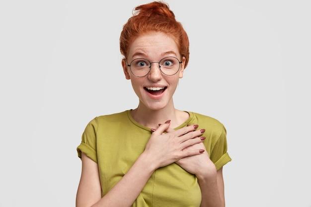 Позитивно удивленная веснушчатая рыжеволосая женщина чувствует изумление, держит руки на груди, носит круглые очки, стоит у белой стены