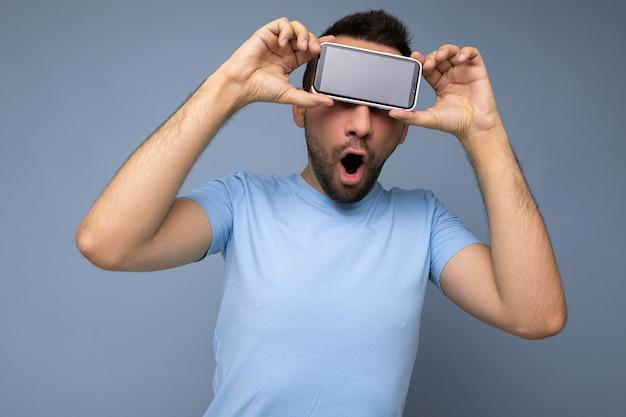 Позитивный изумленный красивый молодой небритый брюнет с бородой в повседневной синей футболке, изолированной на синем фоне, держит и показывает мобильный телефон с пустым дисплеем для макета.