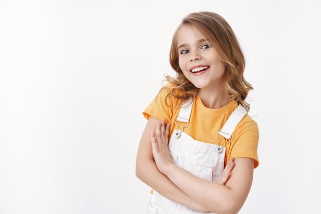 Позитивная амбициозная милая маленькая белокурая девочка, ребенок чувствует себя оптимистично и уверенно улыбается в восторге, смотрит в камеру голубыми глазами, держится за руки, скрестив тело, уверенная поза, стоит белая стена Premium Фотографии