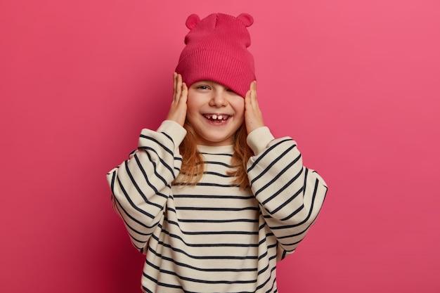 ポジティブな野心的な女の子は、両親が彼女のために新しい帽子を買って、ゆるい縞模様のジャンパーを着て、歯を見せるように微笑んで、他の子供たちと遊んで幸せで、ピンクの壁に隔離されているので嬉しいです。子供の頃、感情