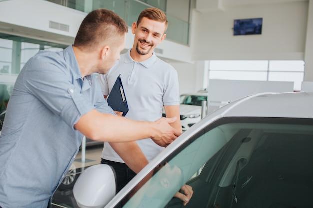肯定的でひげを生やした若い売り手が顧客の前に立ち、彼を見ます。彼は笑っています。買い手が車に触れて売り手を見る。彼は真剣に話している。