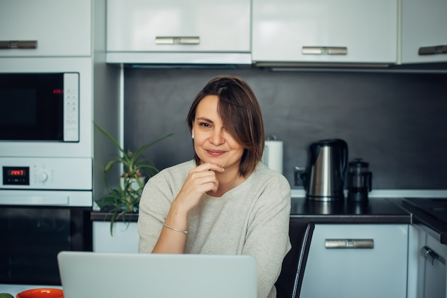 Позитивная и мечтательная писательница работает над любовным романом на домашней кухне. творческий процесс во время самоизоляции и карантина. освоение новых профессиональных навыков, удаленная работа.