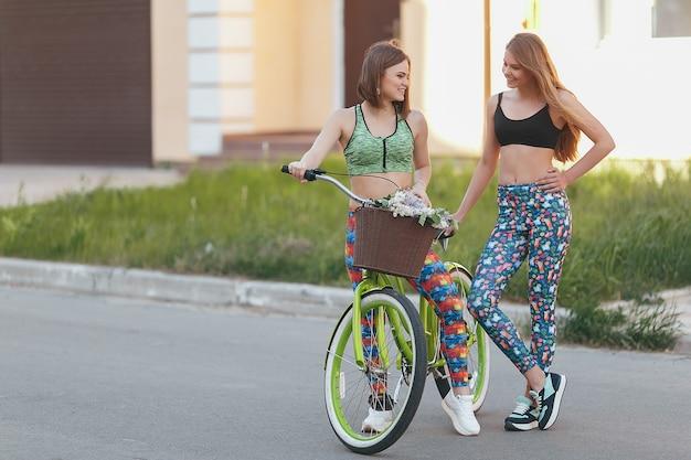 夏の日、路地の公園で自転車で歩いている肯定的で幸せな女性。自転車で通りを歩いている女性の友人。