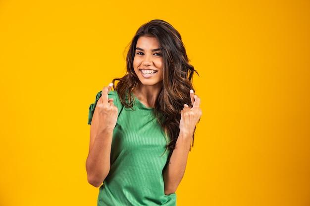 Положительная и счастливая молодая женщина со скрещенными пальцами, желая удачи.