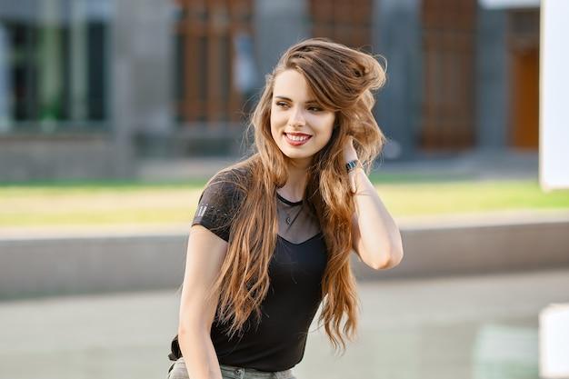長い巻き毛を持つ肯定的で幸せな若い女性