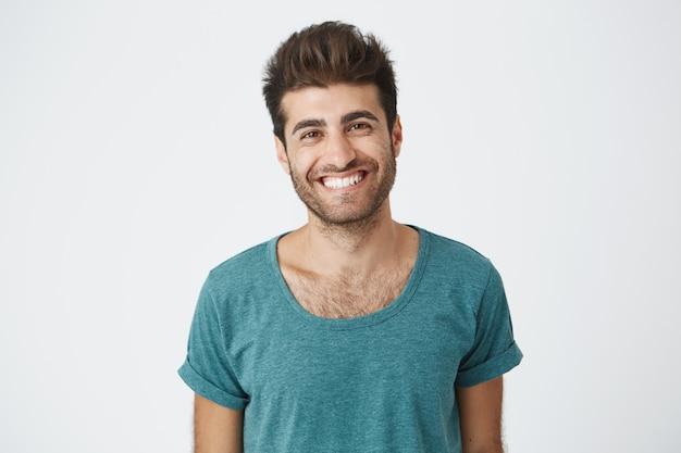 Положительный и радостный испанский человек с бородой, одетый в синюю футболку, ярко улыбаясь, чувствуя себя счастливым по поводу выходного дня на работе. концепция людей и эмоций