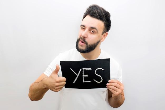 Позитивный и игривый молодой человек стоит и смотрит. он держит черный плакат со словом да. также парень показывает свой большой палец вверх и подмигивает одним глазом.