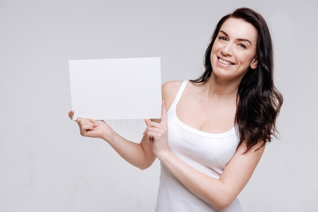 Позитивный подход. фотогеничная изящная активная дама держит в руках белый лист бумаги