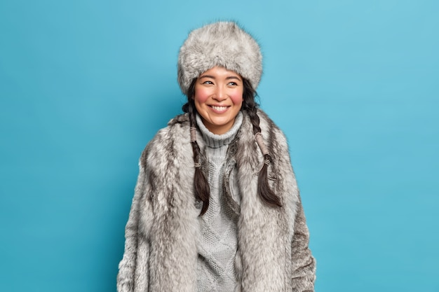 Positive arctic woman with two combed pigtails smiles happily has good mood dressed in warm winter clothes enjoys winter time and walks outdoor during frosty day isolated over blue wall