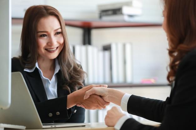 긍정적인 아시아 여성 기업가는 사무실에서 회의를 하는 동안 테이블에 앉아 웃고 악수를 하고 있습니다. 성공 협상 및 비즈니스 계약 완료 개념입니다.